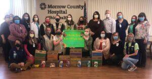Image of Girl Scout Troop members making donation: Zoe, Rebecca, Kaitlyn, Elizabeth, Mary, Kathryn, Macie. Troop leaders are Michelle Montague and Tara Dean.